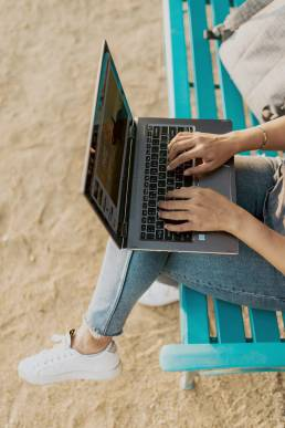 person in blue denim jeans using macbook pro